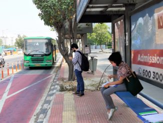 Commuters waiting at a bus stop on the bus priority lane (BPL) along Outer Ring Road, Bengaluru