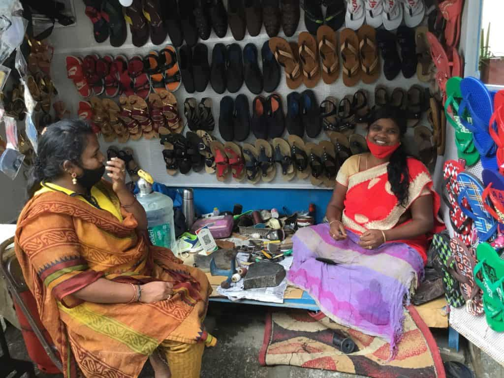 Woman repair cobbler at her workspace on the footpath with a customer