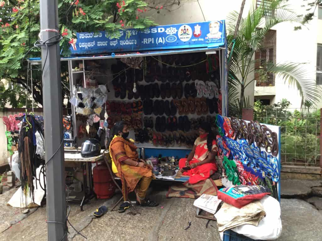 Woman repair cobbler at her workspace on the footpath