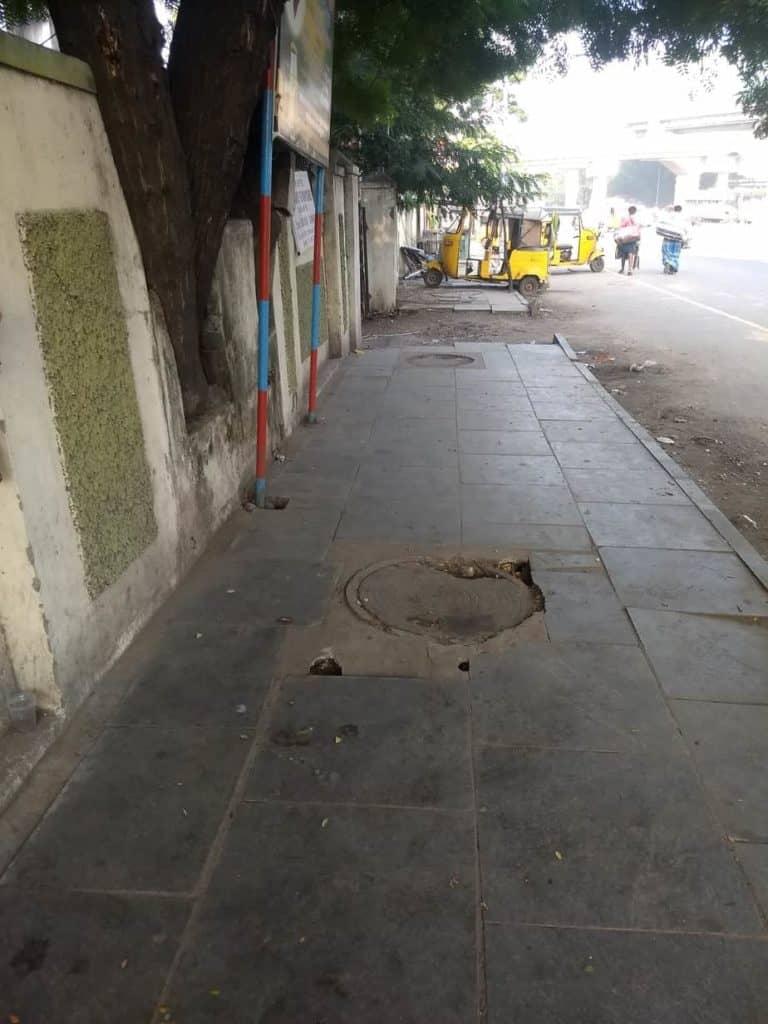 A badly finished manhole sinks on a footpath