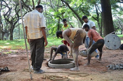 Mannuvaddars adding the finishing touches to a well in Cubbon Park.