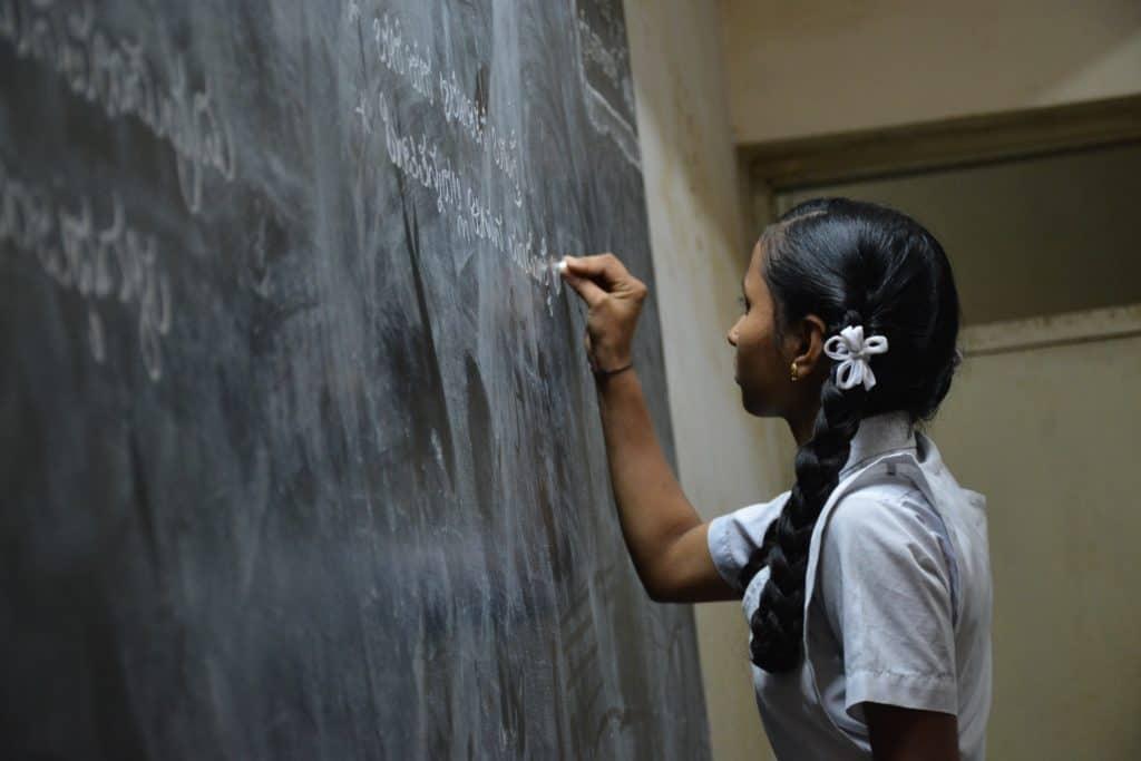 Schoolgirl in front of a blackboard