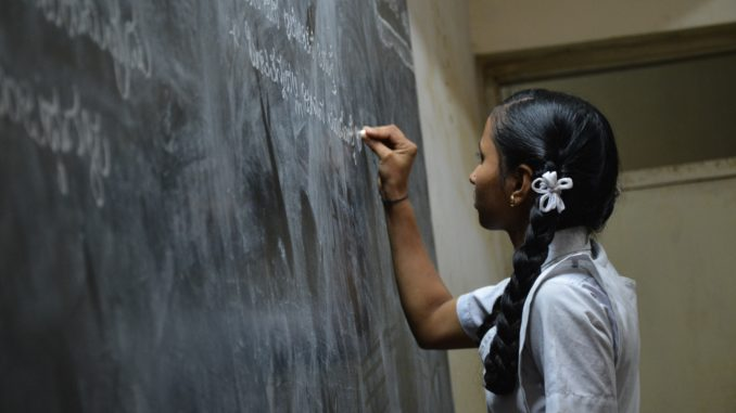 Schoolgirl in front of a blackboard