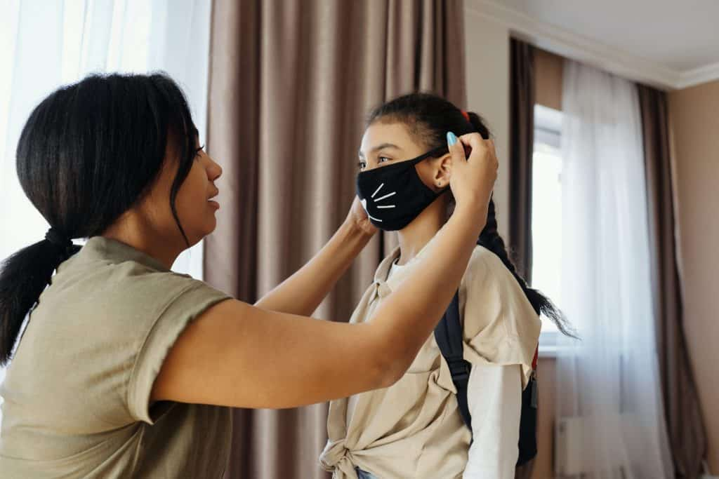 a woman placing a mask on a young girl