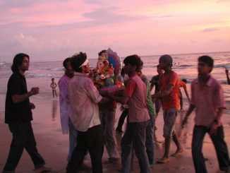 A group of men carry a Ganesh idol to the sea