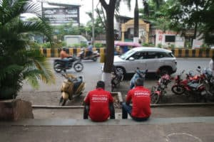 Zomato delivery partners sitting by a pavement