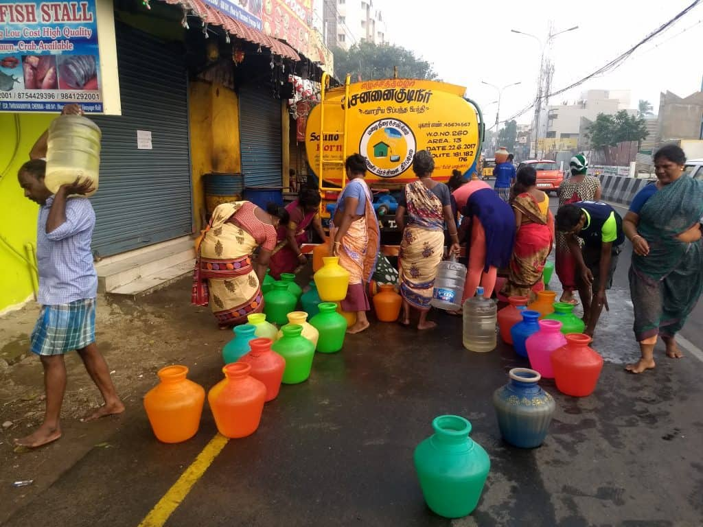 People gather to fill water from the tankers at ECR